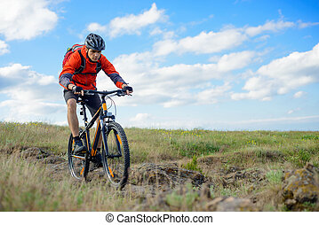 Cyclist in Red Jacket Riding Mountain Bike on the Beautiful Spring Rocky Trail. Extreme Sport Concept