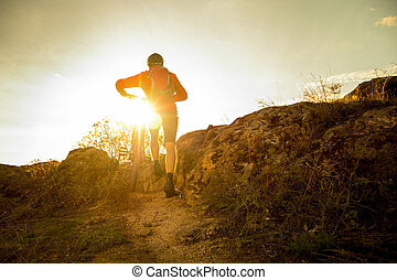 Cyclist in Red Picking his Mountain Bike on Autumn Rocky Trail at Sunset. Extreme Sport and Enduro Biking Concept.