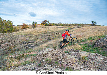 Cyclist in Red Picking the Bike up on Autumn Rocky Trail. Extreme Sport and Enduro Biking Concept.
