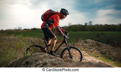 Cyclist in Red Riding Bike on the Rocky Trail at Evening. Extreme Sport and Enduro Biking Concept.