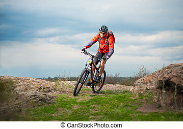Cyclist in Red Riding Bike on the Rocky Trail. Extreme Sport and Enduro Biking Concept.