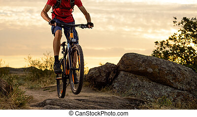 Cyclist in Red Riding the Bike on the Rocky Trail at Sunset. Extreme Sport and Enduro Biking Concept.