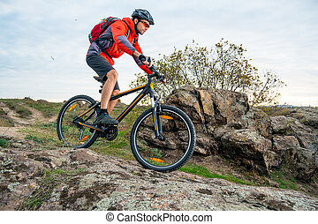 Cyclist in Red Riding the Mountain Bike down Autumn Rocky Trail. Extreme Sport and Enduro Biking Concept.