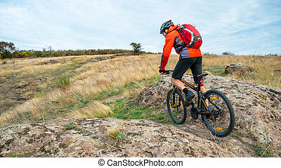 Cyclist in Red Riding the Mountain Bike on Autumn Rocky Trail. Extreme Sport and Enduro Biking Concept.