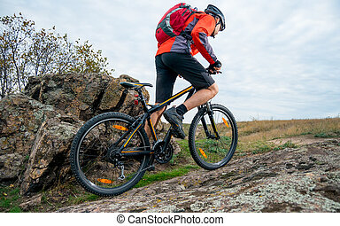 Cyclist in Red Riding the Mountain Bike up Autumn Rocky Trail. Extreme Sport and Enduro Biking Concept.