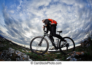 Cyclist in the black sportwear riding the bike on the rock at evening against beautiful blue sky with clouds.