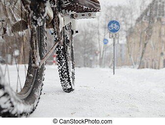 Cyclist in winter with bike road sign low angle