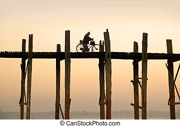 cyclist is driving over U Bein's Bridge in the early morning