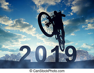 Cyclist jumping on the bicycle at sunset. New Year 2019 concept.