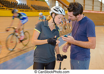 Cyclist looking at stopwatch with trainer