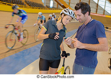Cyclist looking at time on coach's stopwatch