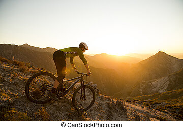 Cyclist man riding mountain bike at sunset