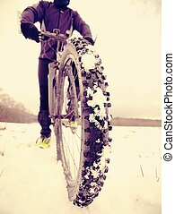 Cyclist man with winter bike stays in snow. Winter extreme sportive concept.