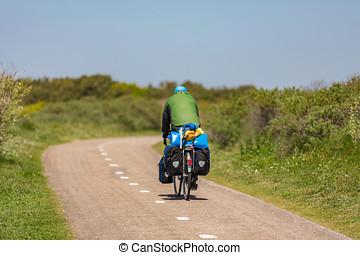 Cyclist on a bike path in the dunes of Noordwijk