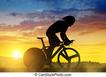 Cyclist on a road racing bike at sunset.