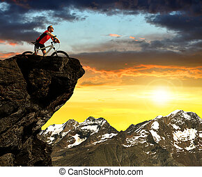Cyclist on bike at sunset in Pennine Alps, Switzerland.