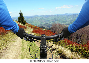 cyclist on bike rides on a mountain road
