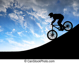 cyclist on downhill bike - silhouette of the cyclist on...