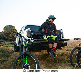 Cyclist on Pickup Off Road Truck Resting after Bike Riding in the Mountains and Talking with Friends