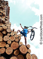 fit man with his bicycle climbing on top of large pile of logs