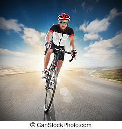 Cyclist on road - Cyclist with helmet pedaling faster on...