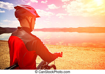 cyclist on the shore of a mountain lake