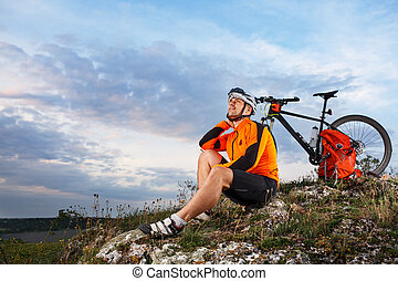 Cyclist resting on grass in mountains. Man is looking aside.