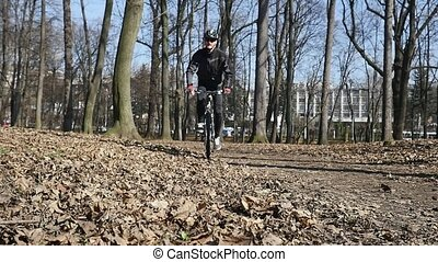 cyclist rides in the park. Autumn leaves on the ground.