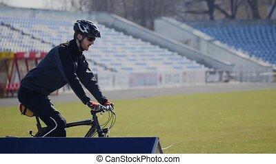 cyclist rides on a stadium.