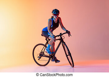 Cyclist riding a bicycle isolated against gradient light pink yellow neon background