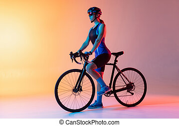 Cyclist riding a bicycle isolated against neon background