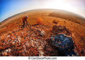 Cyclist riding a bike on an off road to the sunset. Wild landscape