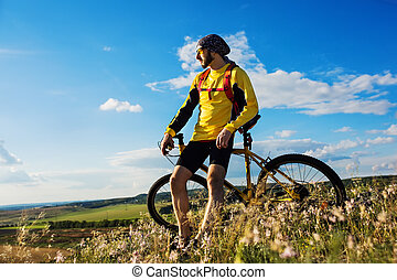 Cyclist riding a bike on off road to the sunset