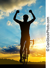 Cyclist riding a road bike at sunset.