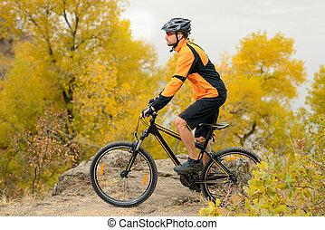 Cyclist Riding Bike on the Beautiful Autumn Mountain Trail