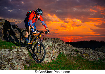 Cyclist Riding Mountain Bike Down Spring Rocky Hill at...