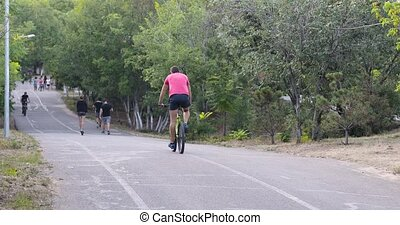 Cyclist riding on road bike, people walk in the park on a summer sunny day, rear view