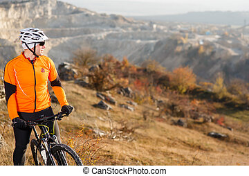 Cyclist Riding the Bike Down Rocky Hill. Extreme Sport Concept. Space for Text.