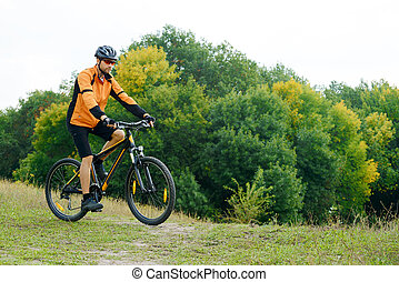 Cyclist Riding the Bike in the Beautiful Autumn Forest