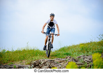Cyclist Riding the Bike on Beautiful Spring Mountain Trail