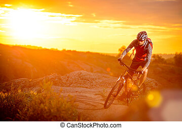 Cyclist Riding the Bike on Mountain Rocky Trail at Sunset -...