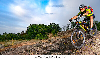 Cyclist Riding the Bike on Rocky Trail at Sunset. Extreme Sport and Enduro Biking Concept.