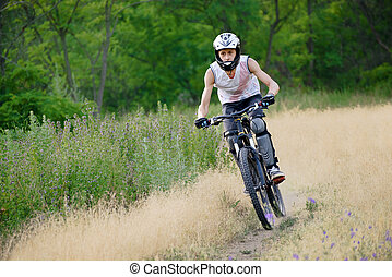 Cyclist Riding the Bike on the Trail in the Beautiful Forest