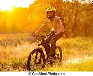 Cyclist Riding the Bike on Trail in the Summer Forest at Sunrise