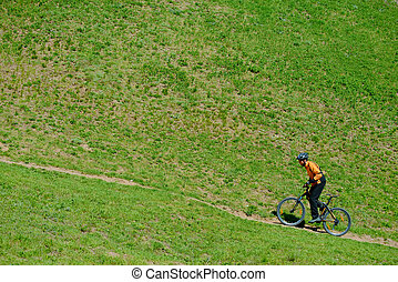 Cyclist Riding Up the Green Hill on the Offroad Trail