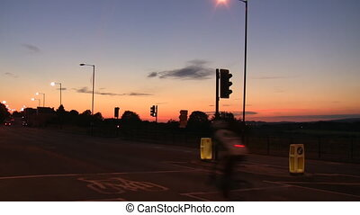 A man cycling through the junction with traffic lights at night with a safety equipment.