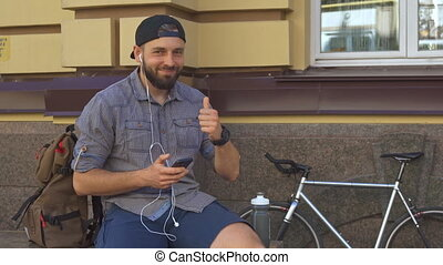 Cyclist shows his thumb up on the street