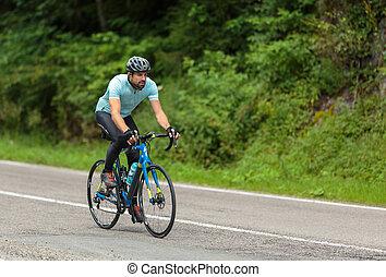 Cyclist speeding on a fast road bike