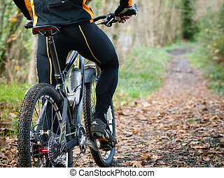 Cyclist standing in front of a path of the forest with a...