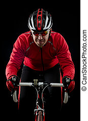 Cyclist on road bike on black background.